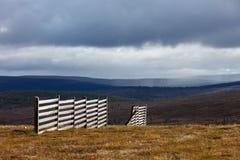 Snow fence. Burst of sunlight illuminates a snow fence on the slopes of Kaunispää fell in the Finnish Lapland royalty free stock image