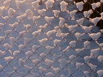 Snow on the fence. Snow-covered lattice fence. White hat air of snow and the contrast of cold metal Stock Images