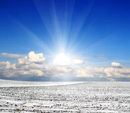 Snow field and blue cloudy sky Royalty Free Stock Images