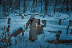 Snow on the field is man with scythe of death. Royalty Free Stock Photography