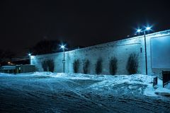Snow filled dark city parking lot at night. Snow filled dark city parking lot next to an industrial vintage building at night Royalty Free Stock Images