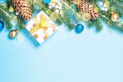 Snow Fir tree branch with blue and golden decorations and present box on blue background. royalty free stock photo