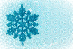 Snow flake. Nice cold toned image of a snow flake on a patterned background Stock Image