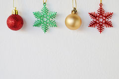 Snow flake and ball ornaments hanging on white wall background Stock Images