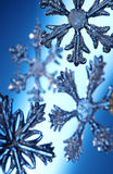Snow Flake Christmas Ornaments. Glass Christmas snow flake ornaments shot on a blue illuminated background Royalty Free Stock Images