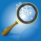 Snow flake and magnifying glass Royalty Free Stock Photo