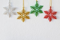 Snow flake ornaments hanging on white wall background Stock Images