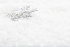 Snow flake on snow background. Silver snow flake on snow background Royalty Free Stock Image