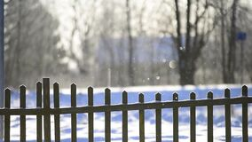 Snow flakes falling in bright sunlight on winter snow covered fence in countryside. defocus effect. stock video footage
