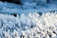 Snow flakes and frost creation on the lava stones. Winter frosty ground and black lava stones with the frost and snow flakes on it with blue blur background Stock Photo