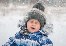 Little boy on snowy day playing snowballs royalty free stock images