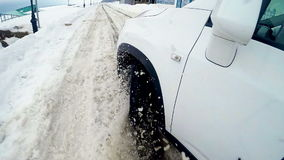 Snow flies into camera. Tire slipping and sliding on snow. On board camera. Close up. stock footage