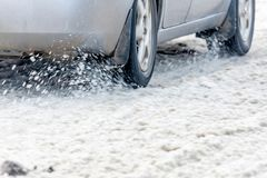 Snow flies from under the wheels of a car traveling along a winter road.  royalty free stock images