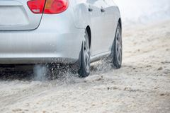 Snow flies from under the wheels of a car traveling along a winter road.  royalty free stock image