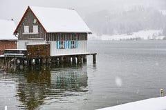 Stilt house at lake by snow flurry. Modern stilt house on a lake by snow flurry in winter royalty free stock image