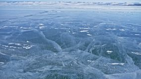 Snow is flying over surface of ice. Snowflakes fly on ice of Lake Baikal. Ice is very beautiful with unusual unique. Cracks. Background view mountain landscape stock video footage