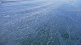 Snow is flying over surface of ice. Snowflakes fly on ice of Lake Baikal. Ice is very beautiful with unusual unique. Cracks. Snow sparkles and glows in red stock video