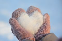 Snow, frosty love in mittens. In the hands of loving heart of, frosty and winter love. Valentine`s in hand. Heart of the snow. Heart in the hands of a loved one Stock Photos