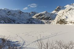 Message Lofoten Planet written in snow of a frozen mountain lake Stock Photos