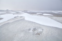 Snow on frozen North sea in Holland Stock Photos