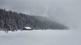 Snow Frozen wooden cabin, Louise Lake, Alberta Canada royalty free stock photo