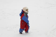 Snow fun. Little child, wearing winter suit, playing in the snow Royalty Free Stock Photos