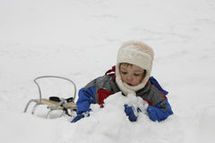 Snow fun. Child playing with sled in the snow Royalty Free Stock Photos