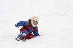 Snow fun. Little child, wearing winter suit, playing in the snow Royalty Free Stock Image