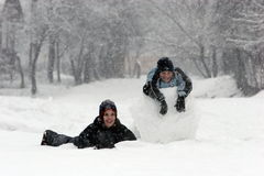 Snow fun 3. Girl and boy and a huge snowball royalty free stock images