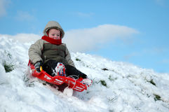 Snow Fun!. Happy little boy (3) on a sleigh sliding down a slope in the snow Stock Image