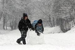 SNOW FUN. Girl and boy rolling a huge snowball royalty free stock images