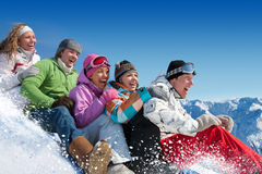 Snow games. Group of  teenagers slide downhill in winter resort Royalty Free Stock Image