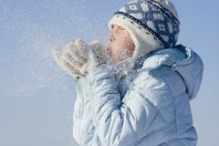 Snow games. Girl playing with snowflakes Stock Photo