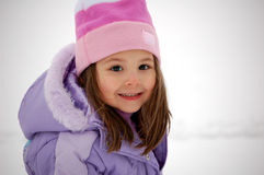 Snow Girl. Four year old girl smiling as she takes a walk outside in the snow.  She is dressed in a pink hat and purple winter coat Stock Images