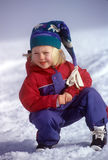 Snow Girl In Snowsuit And Cap. Portrait of a smiling young girl playing in snow, wearing a snowsuit and stocking cap stock photo