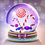 Snow glass crystal ball with christmas lollipops and candycanes Royalty Free Stock Photo