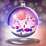 Snow glass crystal ball with christmas lollipops and candycanes Royalty Free Stock Photography