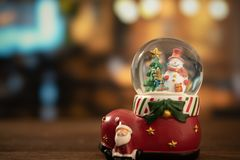 Snow globe ball. Christmas tree and snowman in snow globe ball with bokeh background stock image
