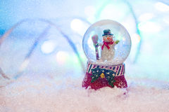 Snow globe with happy snowman blured background Royalty Free Stock Photography