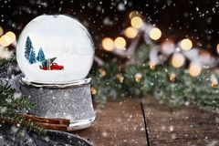 Snow Globe with Old Pick Up Truck. Rustic image of a snow globe with old pick up tuck hauling a Christmas tree surrounded by pine branches, cinnamon sticks and a royalty free stock photo