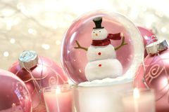Snow globe with pink balls. Snow globe with pink christmas balls and white lights in background stock photography