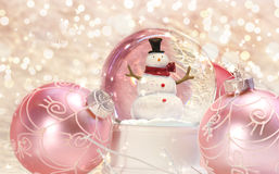 Snow globe with pink ornaments Royalty Free Stock Photos