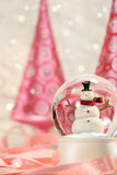 Snow globe with pink trees. Snow globe with pink christmas trees in a winter white background royalty free stock photos