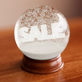 Snow globe with sale word inside. On wooden table Royalty Free Stock Photos