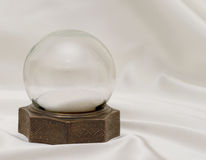 Snow Globe on Satin. Very old antique snow globe with brass base on white satin stock image