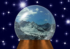 Snow globe with snow-covered mountain tops. Snow globe with miniature model of snow-covered mountain tops and blue sky inside, on dark blue background Royalty Free Stock Images
