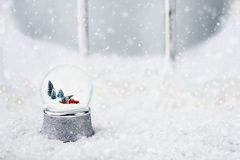 Snow Globe with Toy Truck. Silver snow globe with antique toy truck hauling a Christmas tree. Snowglobe is sitting outdoors on the ledge of an old wooden window Royalty Free Stock Images