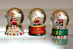 Snow Globe Trio. A Bear dressed a Santa, Santa himself and a penguin Stock Image