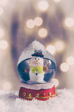 Snow Globe. Vintage snow globe with snowman over christmas lights background Royalty Free Stock Photos