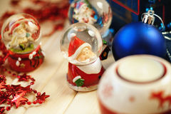 Snow globes and christmas balls. On a table Royalty Free Stock Photo